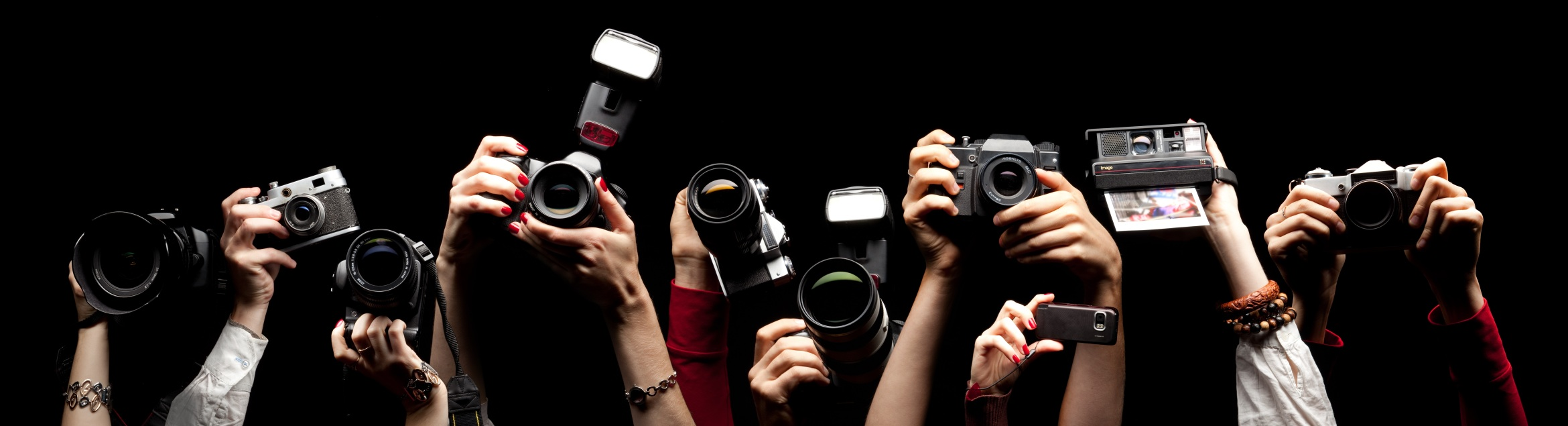Raised hands holding different photocameras